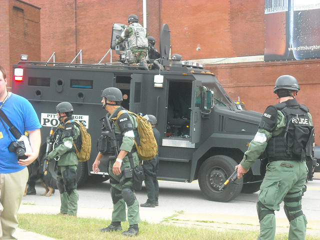 police in combat fatigues in downtown Pittsburgh with LRAD mounted on trudk