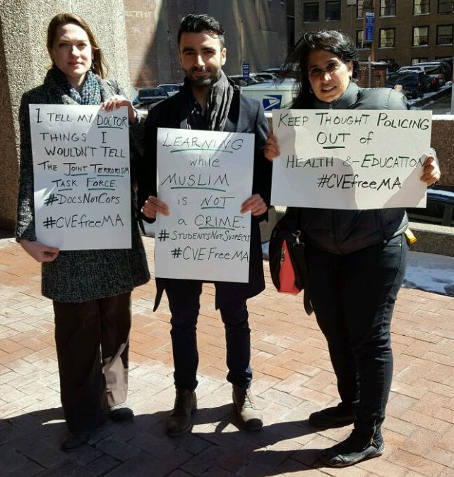 """activists with signs such as """"Learning while Muslim is not a crime"""" and #CVEFreeMA"""