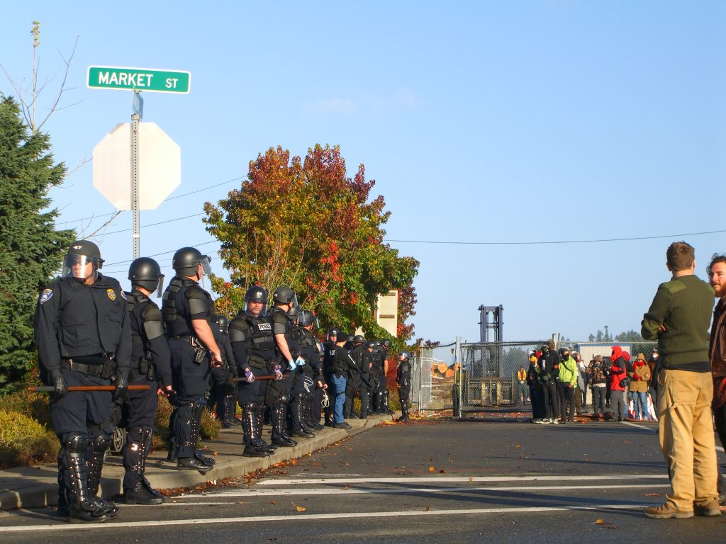 police line up outside army base where protesters are