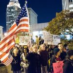 a large protest crowd with US flag and signs promoting solidarity against hate