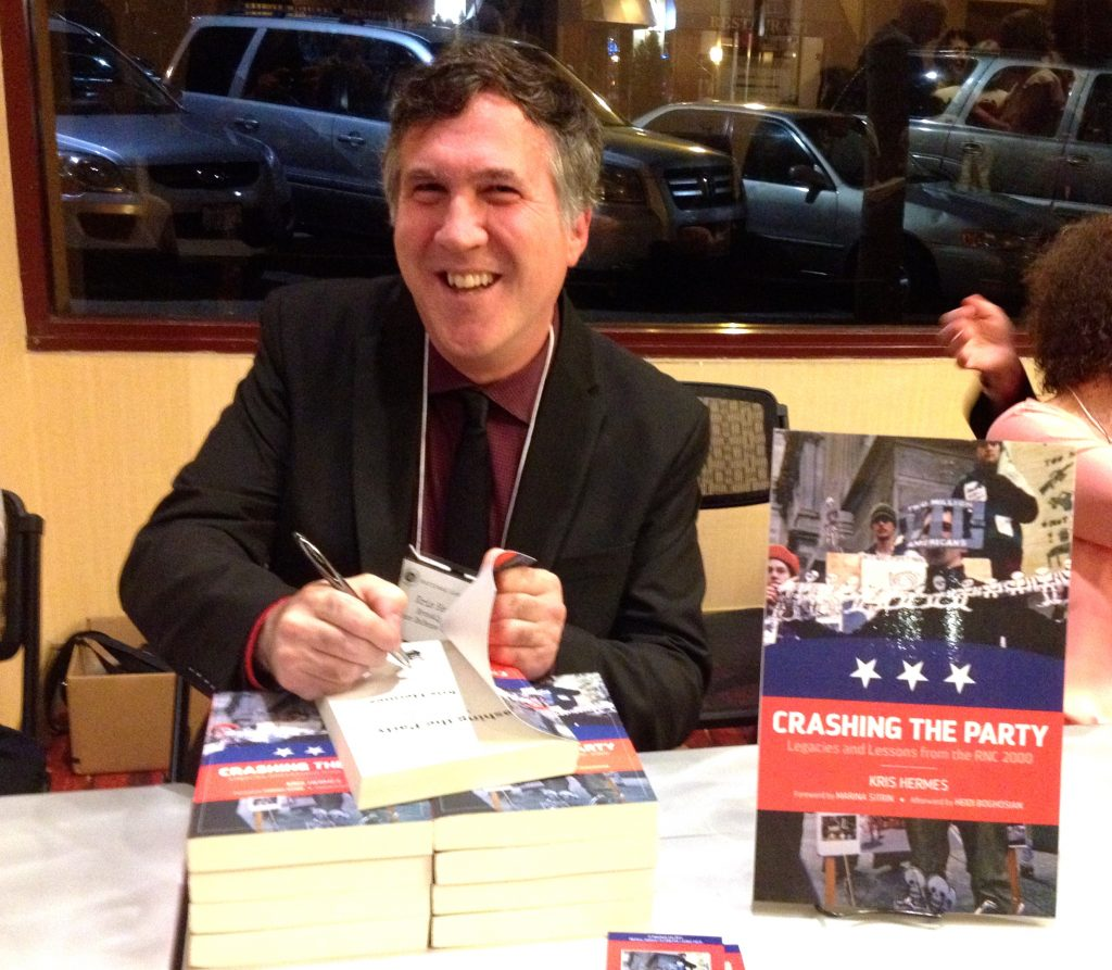 """Kris Hermes signs his book """"Crashing the Party"""""""